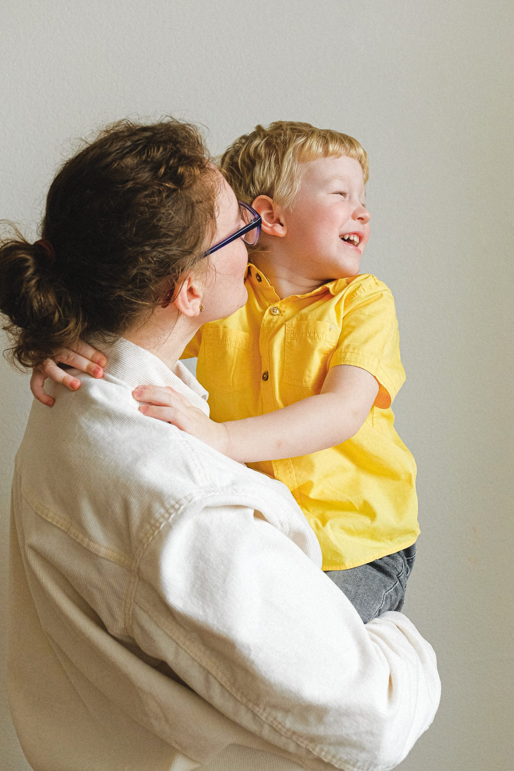 woman-carrying-boy-wearing-yellow-polo-shirt-3905790